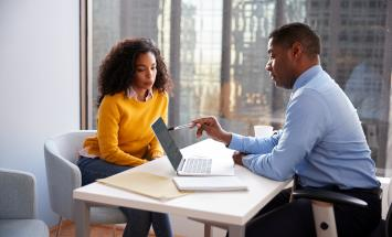 Two people on opposite sides of a table looking at a laptop
