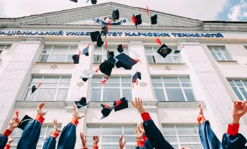 people throwing their graduation caps in the air