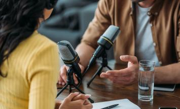 Man and woman conducting a podcast interview