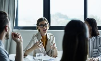 woman speaking to group at table
