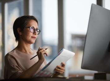Woman looking at her computer while hand-writing on a notepad