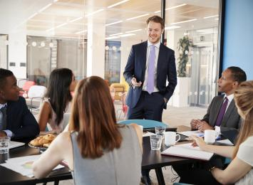 Person standing in front of a table of five people in business suits