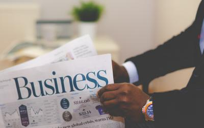 Person holding Business section of newspaper
