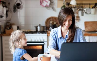 Person with a child in the kitchen on a laptop smiling